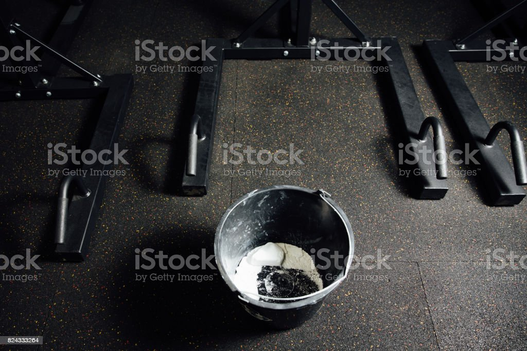 Black bucket with chalk and talc for hands against sliding stock photo