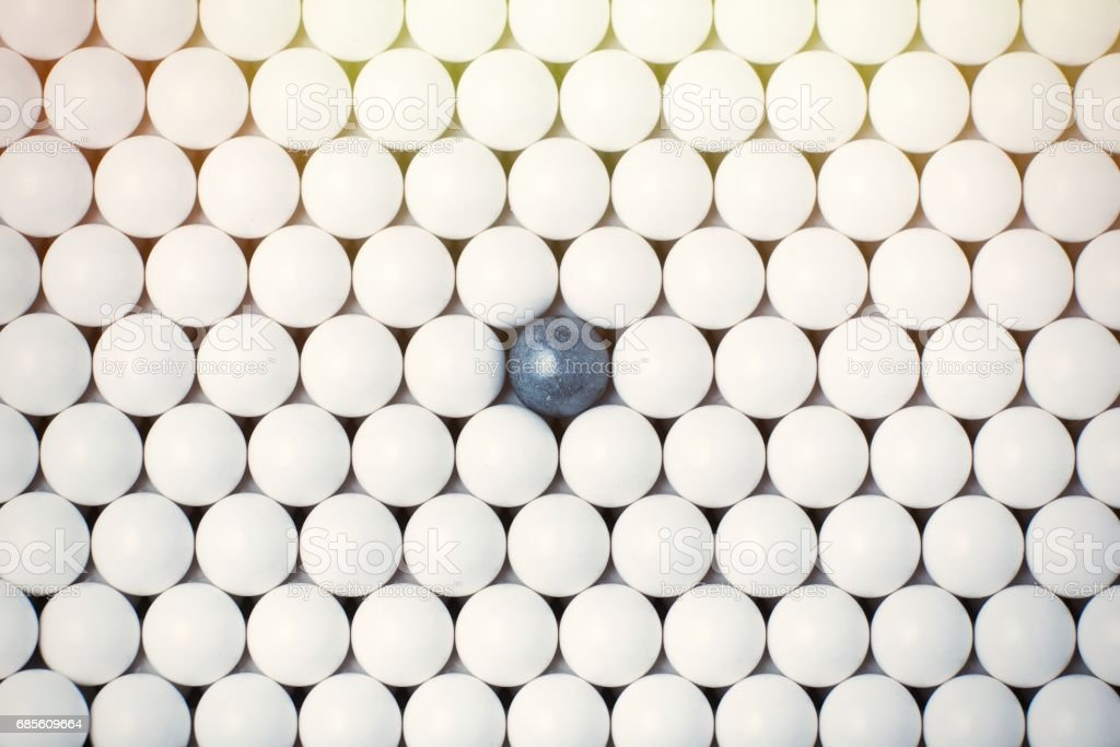 Black bulb among many white ones. Background of airsoft balls stock photo