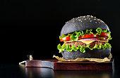 istock Black burger on wooden cutting board 684063810