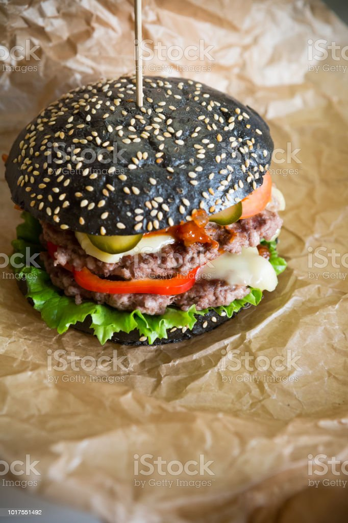 Black burger on wrapping paper stock photo