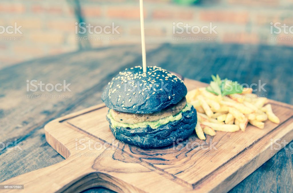 Black burger with french fries in a wooden plate. stock photo