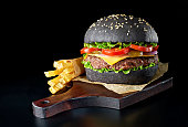 istock Black burger with french fries on wooden cutting board 684063732