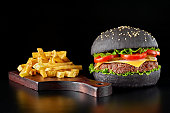 istock Black burger with french fries on wooden cutting board 684063734