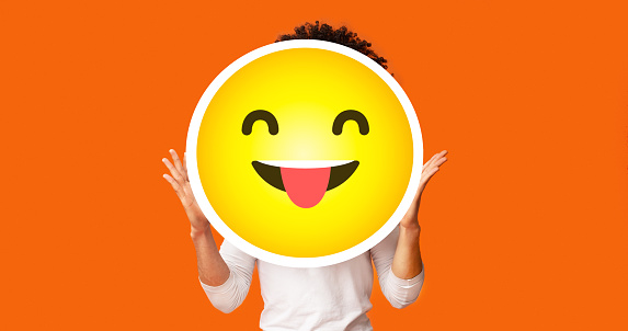 istock Black bushy man holding happy cheeky emoji emoticon in front of head 1269074757