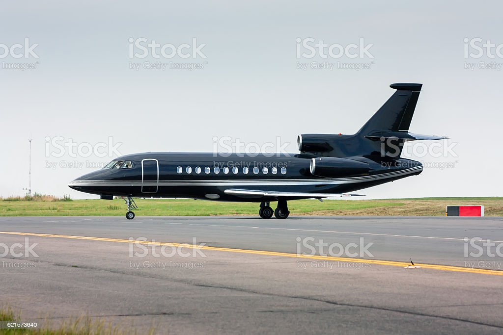 Black business jet taxiing from the runway стоковое фото