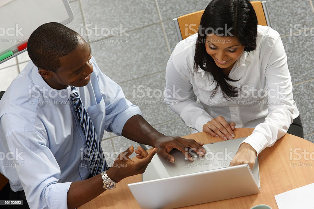 Black Business mentor working with client on laptop in office royalty-free stock photo