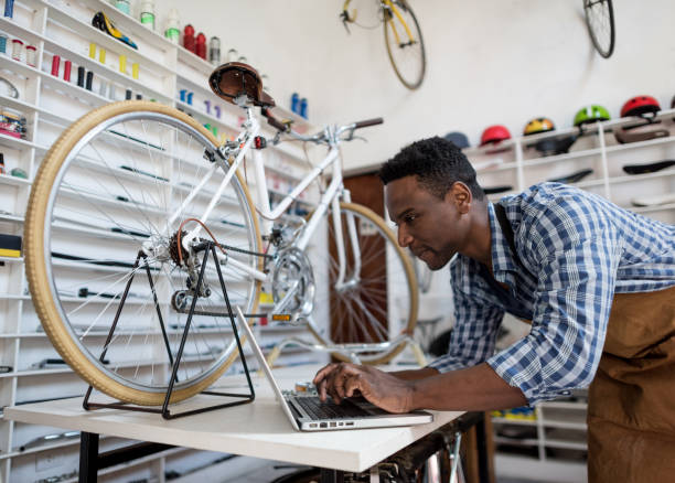 Black business owner of a bike shop checking the online orders on a laptop looking very happy Black business owner of a bike shop checking the online orders on a laptop looking very happy and smiling bicycle shop stock pictures, royalty-free photos & images