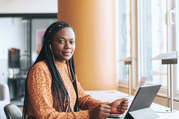 black business woman with head phones and digital tablet in the office stock photo