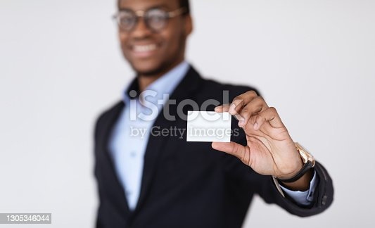 istock Black businessman holding blank card for clients 1305346044