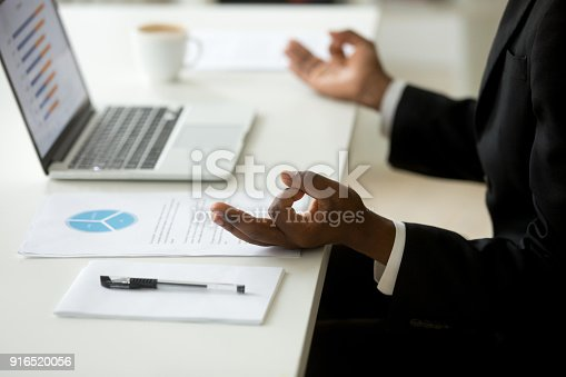 916520034istockphoto Black businessman in suit practicing yoga at workplace, close up 916520056