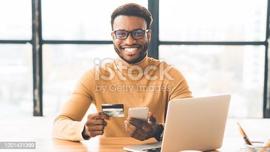 istock Black businessman making purchases using smart phone 1201431399