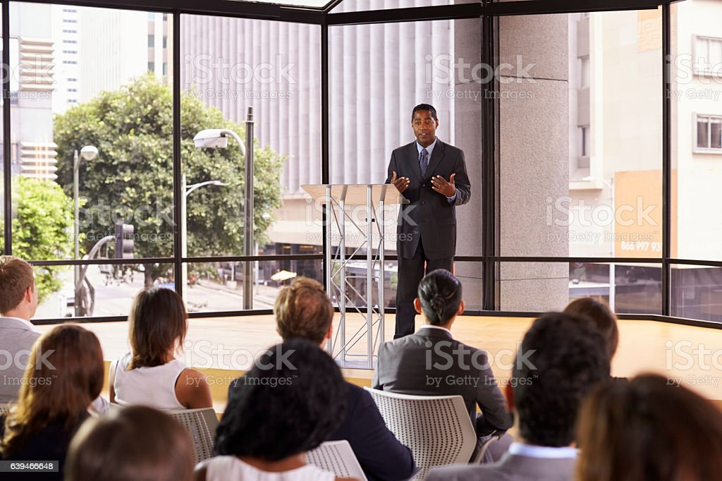 Black businessman presenting seminar gesturing to audience photo libre de droits