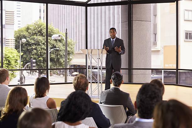 Black businessman presenting seminar gesturing to audience stock photo
