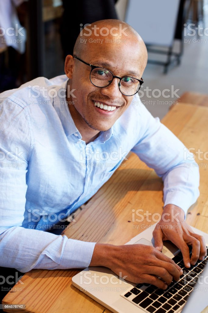 black businessman sitting with laptop stock photo