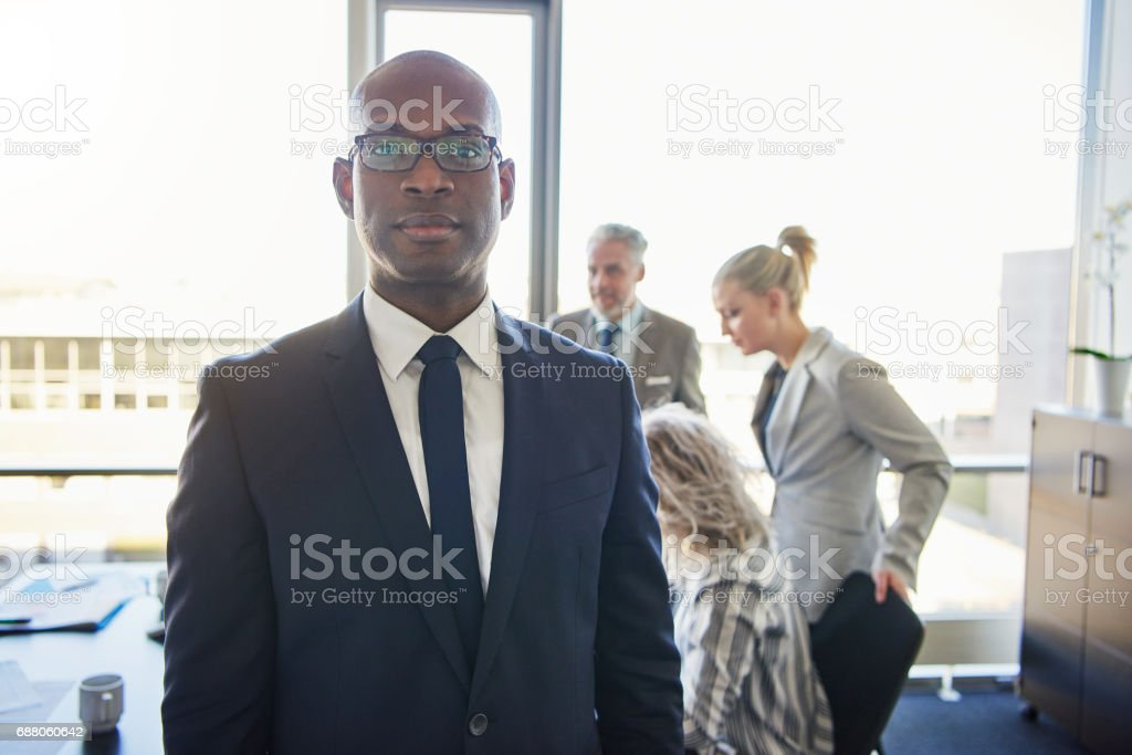 Black businessman standing in front of team stock photo