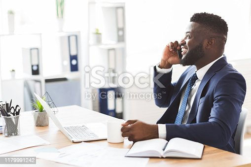 Smiling young black businessman talking on mobile phone, drinking coffee in modern white office, copy space