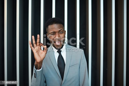 Attractive African American male in gray suit winking and showing OK gesture while standing near striped wall inside modern building