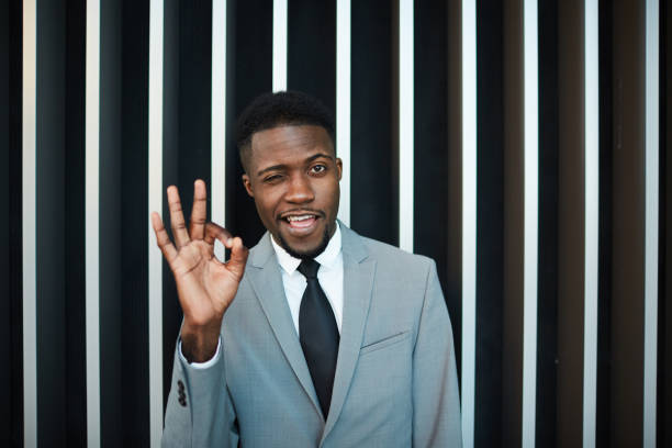 Black businessman winking and gesturing OK stock photo