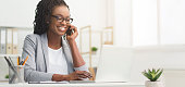 Lady Boss. Afro Businesswoman Talking On Cellphone While Working On Laptop In Modern Office, Wide Horizontal Banner, Panorama With Free Space