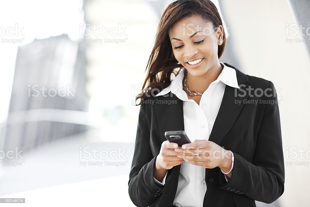 Black businesswoman texting stock photo