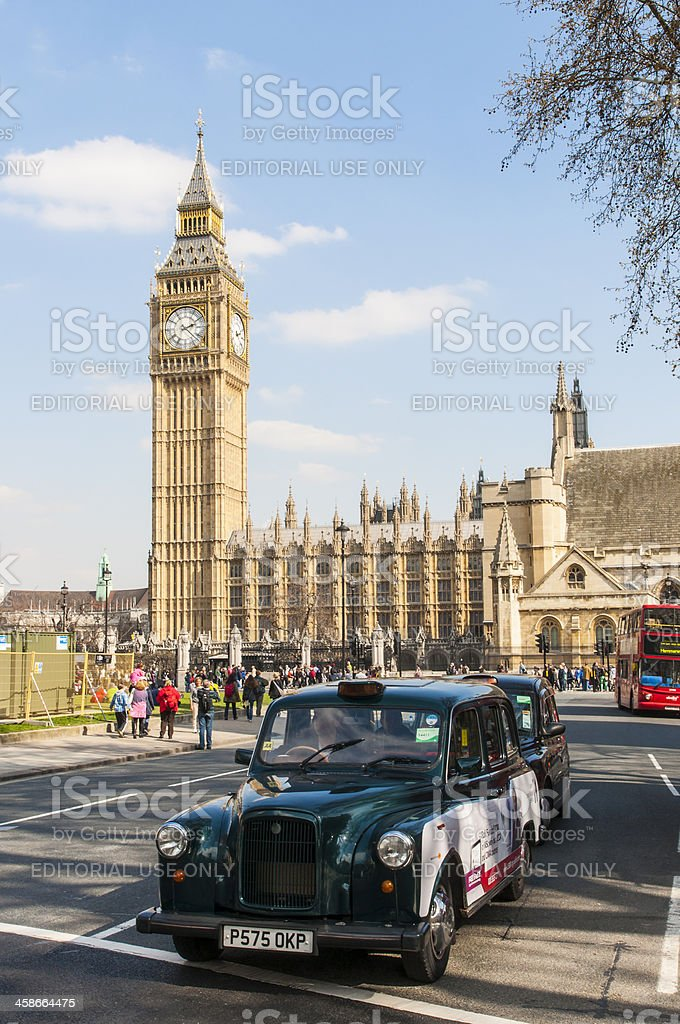 Black cab driving by Houses of Parliament stock photo