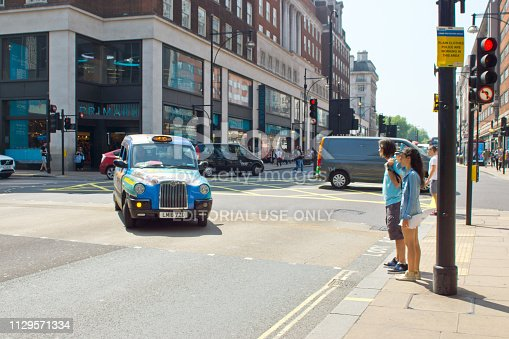 Black cab with advertising on Regent Street, London with shoppers/tourists waiting to cross at a junction.