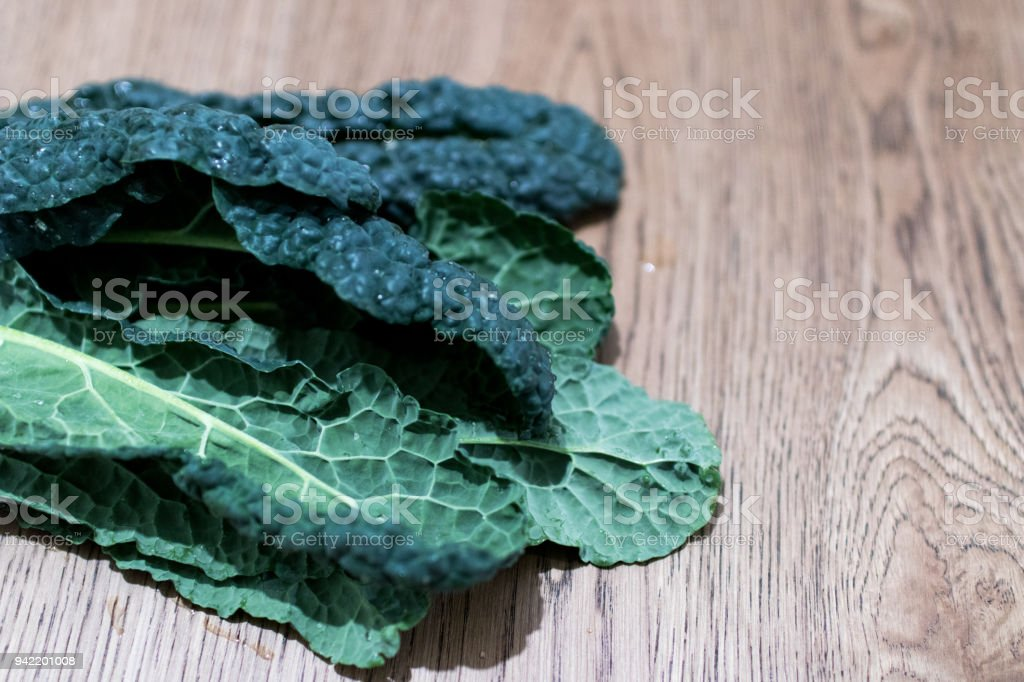 Black cabbage leaves with potatoes on a wooden table stock photo