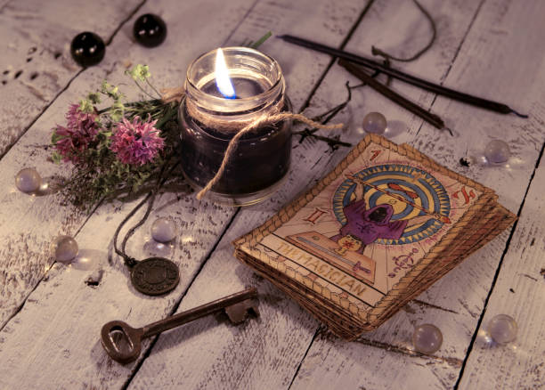 Black candle and old tarot cards on wooden planks stock photo