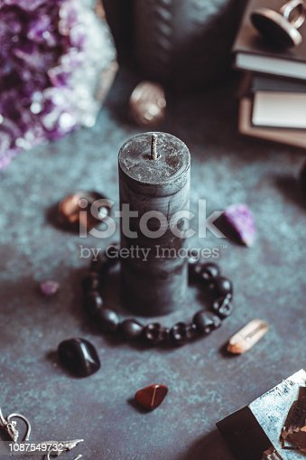 Black candle on a witch's altar for a magical ritual among crystals and black candles.