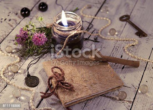 811119304 istock photo Black candle with diary, medallion, key and mystic objects 811119356