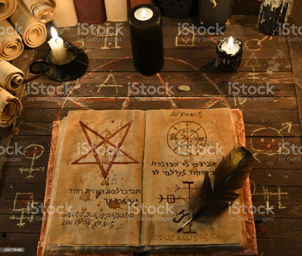 Black candles and open magic book with pentagram stock photo