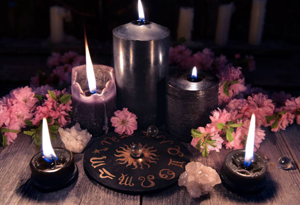 Black candles and zodiac circle with sakura flowers on witch table stock photo