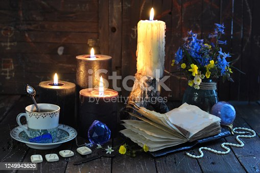 811119304 istock photo Black candles, runes and open diary with empty pages on witch table. 1249943633