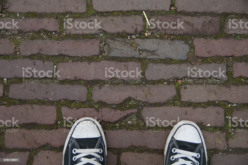 Black canvas sneakers brick street stock photo