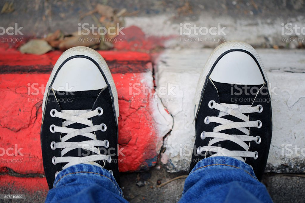Black canvas sneakers on a sidewalk stock photo