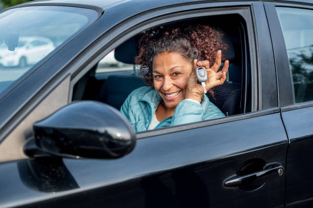 Black car driver woman smiling showing new car keys and car stock photo