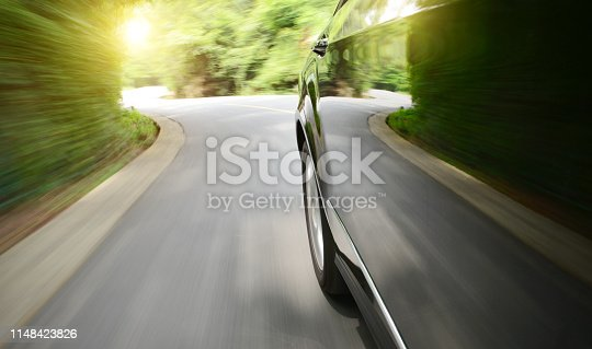 688980174istockphoto Black car driving fast on a mountain road 1148423826