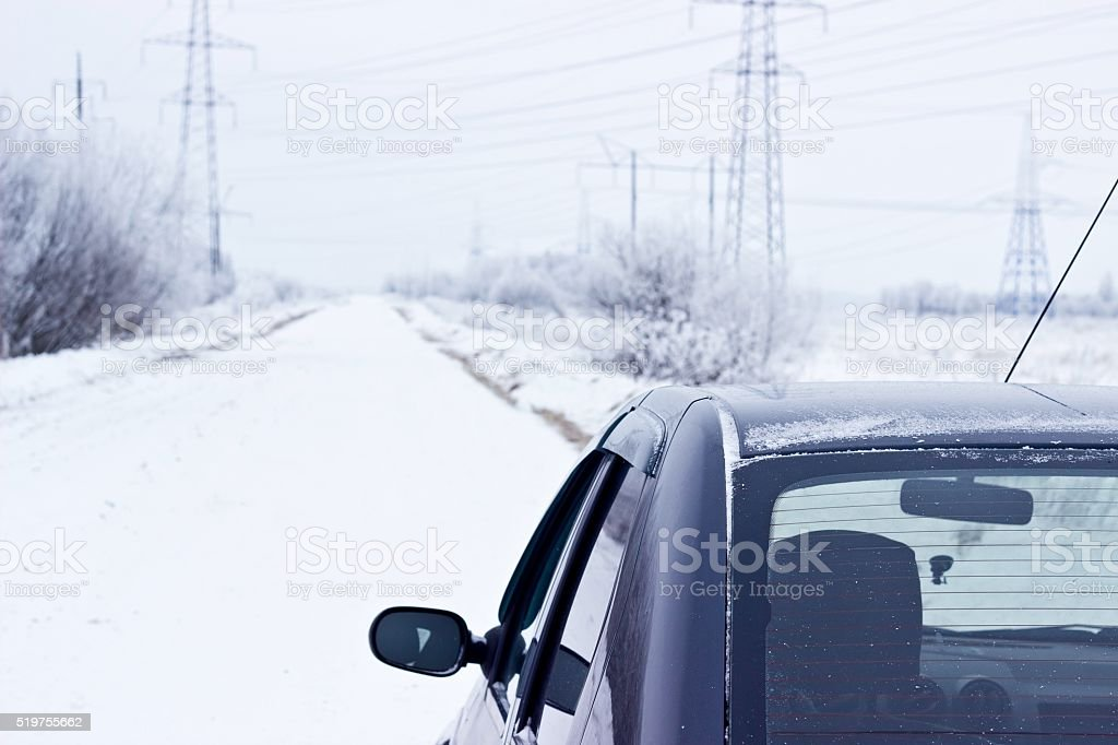 Black car on winter snowy road. Selective focus stock photo
