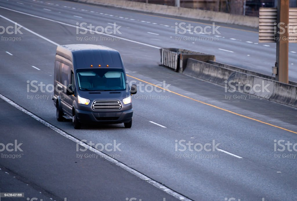 Black cargo mini van running on the multiline road stock photo