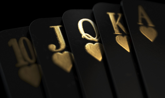 A fanned out royal flush suit of five black casino playing cards with gold markings on a dark classy background - 3D render