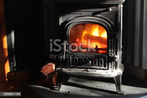 A black cast iron fire place with wood burning inside of it. Keeping warm concept image.