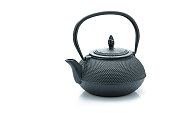 Black cast iron teapot isolated on reflective white background. The composition is at the right of an horizontal frame leaving useful copy space for text and/or logo at the left. Predominant colors are black and white. High resolution 42Mp studio digital capture taken with Sony A7rii and Sony FE 90mm f2.8 macro G OSS lens