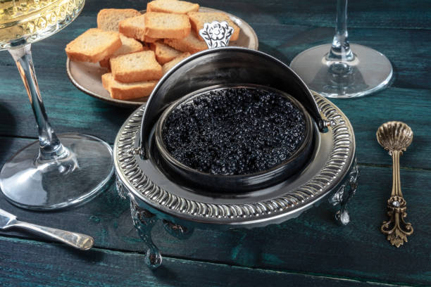 Black caviar in a vintage bowl, with a spoon and bread, on a dark wooden background stock photo