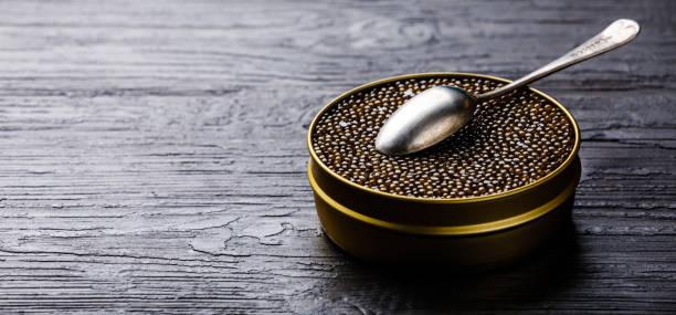 caviar negro en lata y la cuchara de plata - caviar fotografías e imágenes de stock
