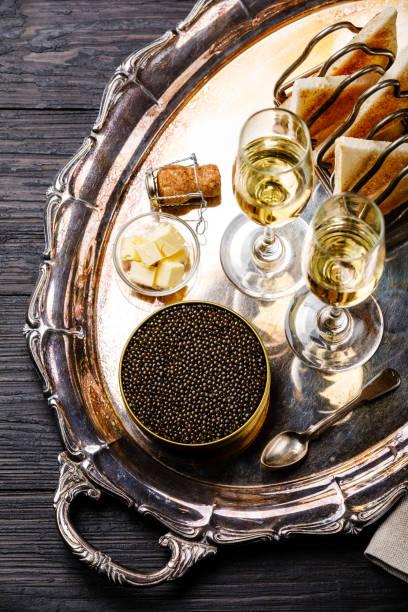 negro caviar en lata, pan fresco tostado y champagne en bandeja de plata - caviar fotografías e imágenes de stock
