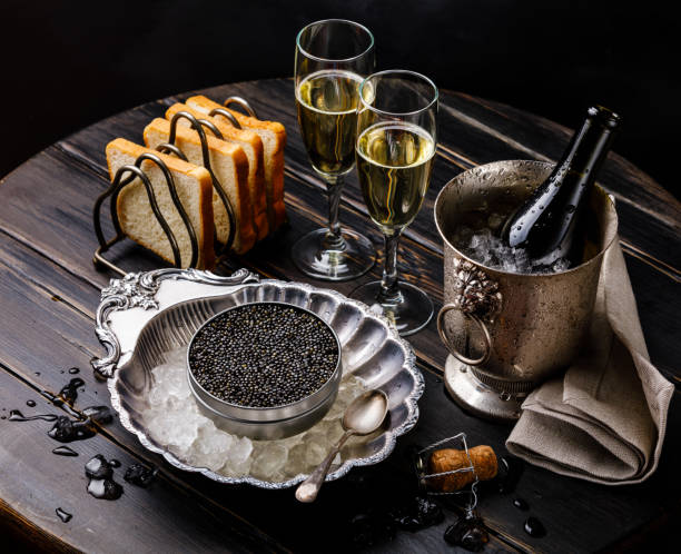 Black caviar in can on ice in silver bowl, bread and champagne in ice bucket stock photo