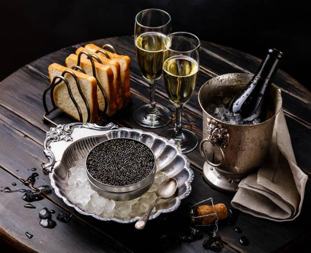 caviar negro en poder en hielo en el tazón de plata, pan y champagne en cubo de hielo - caviar fotografías e imágenes de stock