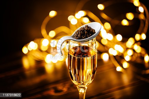 Black caviar in porcelain spoon and glass of champagne Buffet table style on Holiday Christmas sparkling lights background bokeh