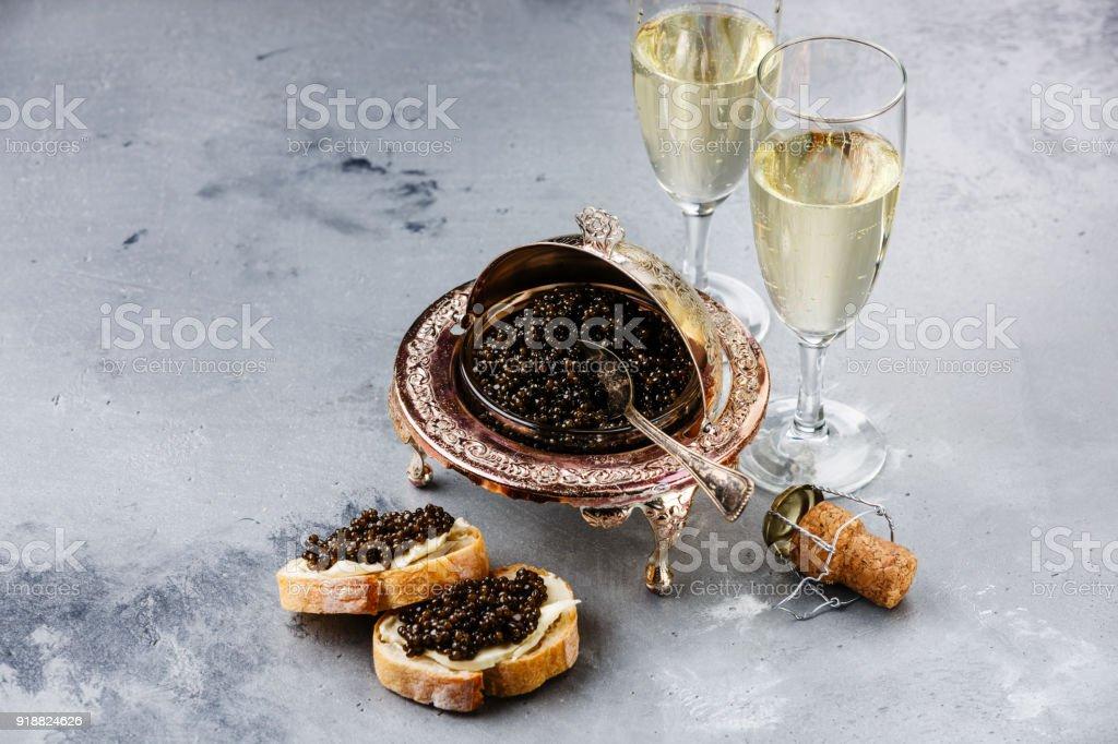 Black caviar in silver bowl, sandwiches and champagne stock photo