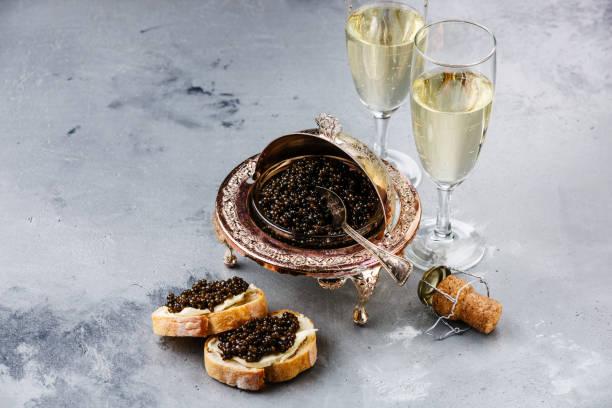 caviar negro en tazón de fuente de plata, sándwiches y champagne - caviar fotografías e imágenes de stock